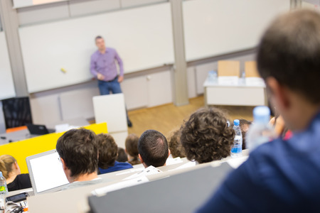 Professor giving presentation in lecture hall at university. Participants listening to lecture and making notes.