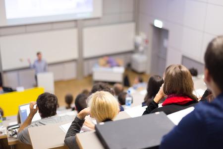 Profesor dávat prezentace v přednáškovém sále na vysoké škole. Účastníci poslouchat přednášky a dělat si poznámky.