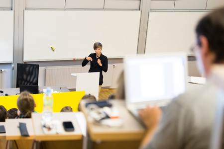 college: Speaker giving presentation in lecture hall at university. Participants listening to lecture and making notes. Stock Photo
