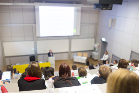 Speaker giving presentation in lecture hall at university. Students listening to lecture and making notes. photo