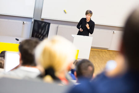 faculty: Speaker giving presentation in lecture hall at university. Participants listening to lecture and making notes. Stock Photo