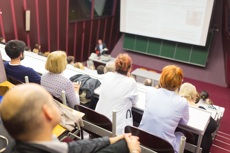 Lecturer at university. Healthcare expert giving a talk to medical faculty professors. Participants listening to lecture and making notes. photo