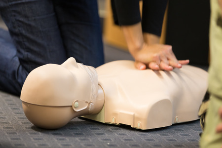 cpr: A group of adult education students practitcing CPR chest compressioon on a dummy. Stock Photo