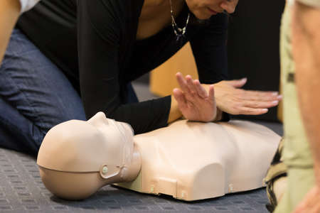 chest compression: A group of adult education students practitcing CPR chest compressioon on a dummy. Stock Photo