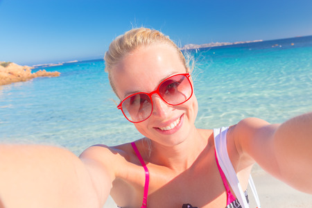 hot girl: Lady taking a selfie on the beach, sending a kiss from summer vacations. Stock Photo