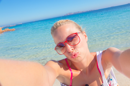sexy blonde woman: Lady taking a selfie on the beach, sending a kiss from summer vacations. Stock Photo