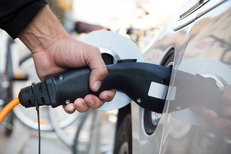 energia electrica: Fuente de alimentaci�n para la carga de coches el�ctricos. Estaci�n el�ctrica de carga del coche. Cerca de la fuente de alimentaci�n enchufado en un coche el�ctrico est� cargando. Foto de archivo