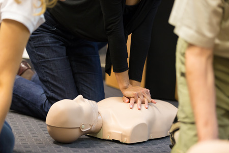first class: A group of adult education students practitcing CPR chest compressioon on a dummy. Stock Photo