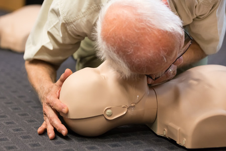 Seniror first aid student practitcing CPR on a dummy.