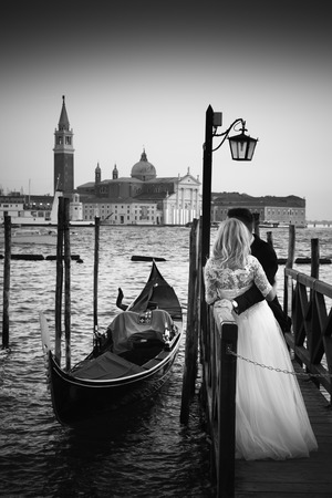 Romantic married couple in Romantic Italian city of Venice in black and white. Traditional Venetian wooden gondola and Roman Catholic church of San Giorgio Maggiore in the background. Standard-Bild