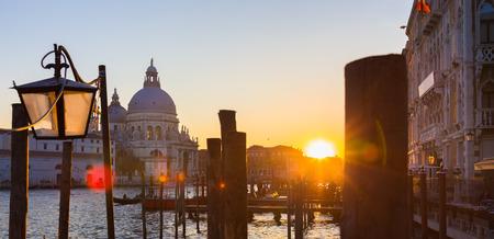 Romantic Italian city of Venice in sunset. World Heritage Site. Traditional Venetian wooden boats, gondolier and Roman Catholic church Basilica di Santa Maria della Salute. photo
