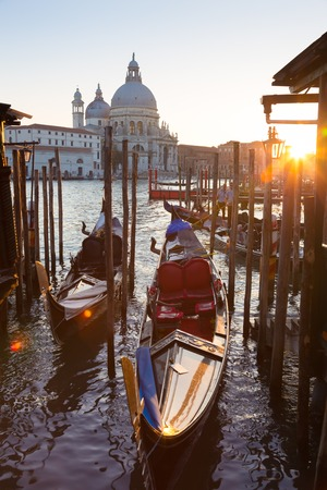 Venice, Italy - October 31, 2014: Traditional wooden boads and a gondolier in the Grand Canal in front of Santa Maria della Salute in sunset.
