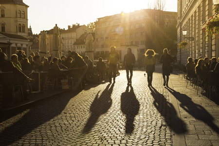 ljubljana: Ljubljana, Slovenia - October 30, 2014: People terracing (sitting, drinking coffee and people watching) in lively Ljubljana city center in the afternoon sun.