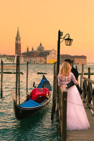 Romantisch getrouwd stel in romantische Italiaanse stad Venetië in zonsondergang. Traditionele Venetiaanse houten gondel en rooms-katholieke kerk van San Giorgio Maggiore op de achtergrond. Stockfoto
