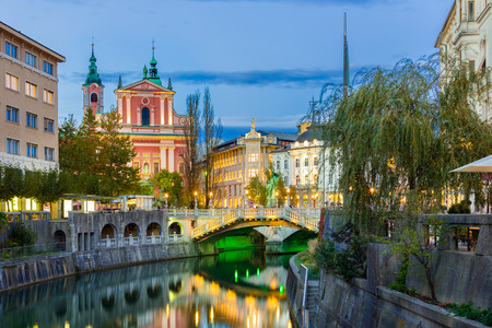 ljubljana: Romantic medieval Ljubljanas city center, capital of Slovenia, Europe. Night life on the banks of river Ljubljanica where many bars and restaurants take place. Franciscan Church in background Stock Photo