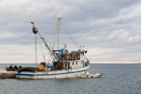 fishing nets: Old rusty fishing boat moored in the harbour. Stock Photo