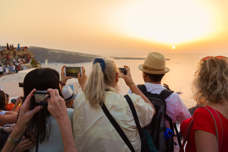 greece: Large group of tourist watching and taking photos of famous sunset view in Oia village on Santorini island in Greece, Mediterranean Europe.
