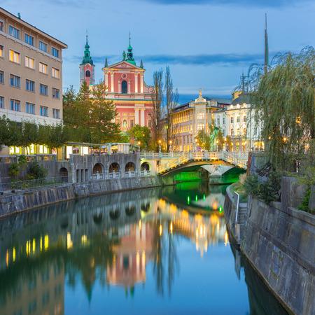 ljubljana: Romantic Ljubljana city center. River Ljubljanica, Triple Bridge - Tromostovje, Preseren square and Franciscan Church of the Annunciation. Ljubljana Slovenia Europe.