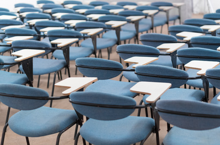seminar room: Interior of empty conference hall with blue velvet chairs with small desks for writing notes.