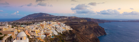 Cityscape of Fira, dramatically located on the edge of the caldera cliff on the island of Thira known as Santorini, Greece. Panorama shot at dusk. photo