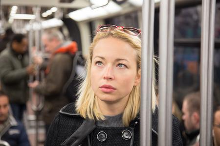 servicios publicos: Bella dama rubia caucásica llevaba abrigo de invierno viajar en metro en hora punta. El transporte público.