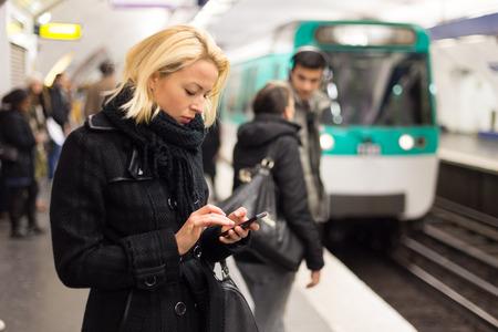 plataforma: Mujer joven en abrigo de invierno con un teléfono celular en la mano esperando en el andén de una estación de ferrocarril para el tren para llegar. Foto de archivo