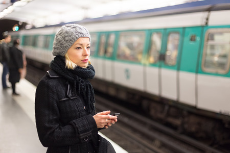 station wagon: Young woman in winter coat with a cell phone in her hand waiting on the platform of a railway station for train to arrive. Public transport. Stock Photo