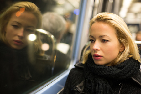 train: Thoughtful lady riding on a subway and looking out the window. Reflection of her face can be seen in the window.