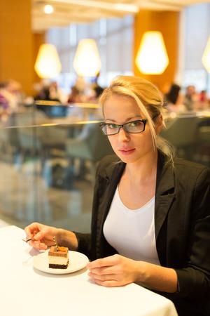 unmarried: Mujer de negocios de comer su postre favorito en un moderno restaurante de lujo del hotel. Incapaz de resistir nuestros dulces vicios. Estilos de vida.