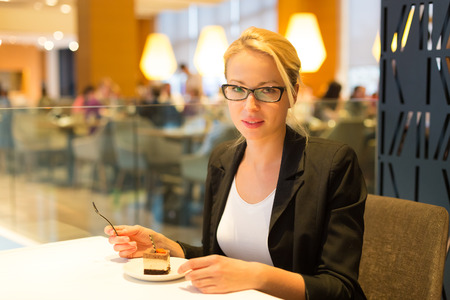 unmarried: Business woman eating her favorite dessert in a fancy modern hotel restaurant. Unable to resist our sweet vices. Lifestyles.