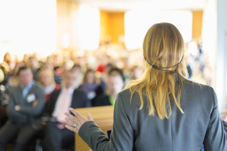conventions: Female speaker at Business Conference and Presentation. Audience at the conference hall. Business and Entrepreneurship. Business woman. Stock Photo