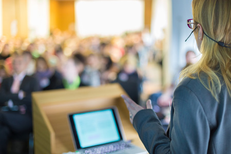 computer speaker: Female speaker at Business Conference and Presentation. Audience at the conference hall. Business and Entrepreneurship. Business woman. Stock Photo
