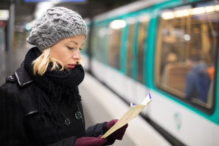 railroad transport: Casually dressed woman wearing winter coat, waiting on a platform for a train to arrive, orientating herself with public transport map. Urban transport. Stock Photo