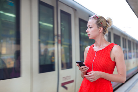 arrive: Young woman in red dress with a cell phone in her hand waiting on the platform of a railway station for their train. to arrive. Stock Photo