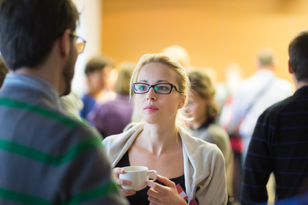 socializing: Peoplegathering and socializing during coffee break at conference meeting.  Business and entrepreneurship.