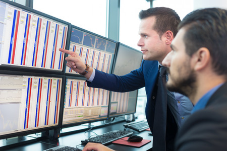 Stock traders looking at graphs, indexes and numbers on multiple computer screens Banque d'images