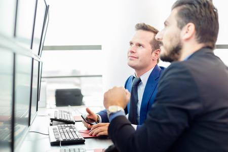 성공적인 기업인 주식을 거래. 주식 거래자는 여러 컴퓨터 화면에 그래프, 인덱스와 숫자를 찾고 있습니다. 상인 사무실에서 동료. 비즈니스 성공. 스톡 콘텐츠