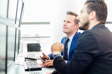business executive: Successful businessmen trading stocks. Stock traders looking at graphs, indexes and numbers on multiple computer screens. Colleagues in traders office. Business success. Stock Photo