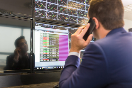 Businessman with cell phone trading stocks. Stock analyst looking at graphs, indexes and numbers on multiple computer screens. Stock trader evaluating economic data. Banque d'images
