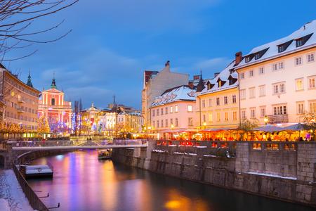 ljubljana: View of lively river Ljubljanica bank and Tromostovje in old city center decorated with Christmas lights at dusk. Ljubljana, Slovenia, Europe.