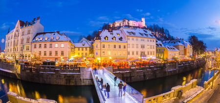 ljubljana: Ljubljana in Christmas time. Lively nightlife in old medieval city center decorated with Christmas lights. Slovenia, Europe. Shot at dusk with fish eye lens. Stock Photo