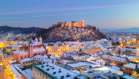 slovenia: Aerial panoramic view of Ljubljana decorated for Christmas holidays. Roofs covered in snow in winter time. Slovenia, Europe.