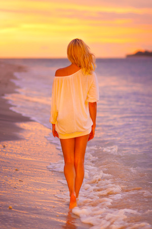 evening glow: Beautiful blonde lady relaxing and enjoying vacations on the sandy beach at sunset. Romantic tropical holidays. Stock Photo