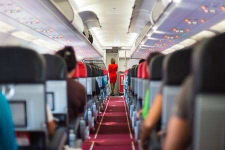 air hostess: Intérieur de l'avion avec des passagers sur les sièges et hôtesse de l'air en uniforme rouge à l'allée.