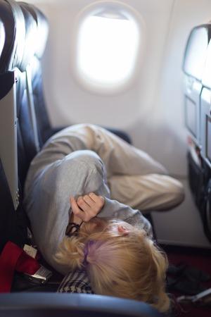 jetliner: Woman sleeping during flight aboard a jetliner airplane.