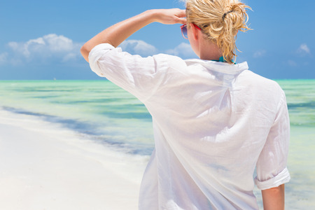 tunic: Happy woman enjoying, relaxing joyfully in summer by tropical blue water. Beautiful caucasian model  wearing white beach tunic on vacations looking down picture perfect Paje beach, Zanzibar, Tanzania. Stock Photo