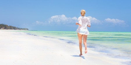 tunic: Happy woman having fun, enjoying summer, running joyfully on tropical beach. Beautiful caucasian model  wearing white beach tunic on vacations on picture perfect Paje beach, Zanzibar, Tanzania.