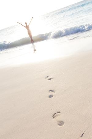 free running: Woman, arms raised, enjoying summer on tropical beach in in sunset. Beautiful caucasian model wearing bikini on vacations on sandy beach. Footprints in sand. Stock Photo