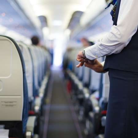 Interior of airplane with passengers on seats and stewardess in uniform waiting at the aisle.