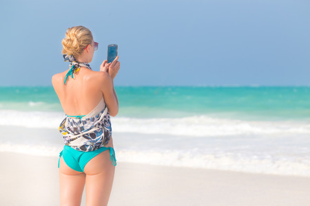 Blonde caucasian woman taking photo of blue tropical beach. Beautiful caucasian model  wearing turquoise swimsuit and colorful scarf on vacations on picture perfect Paje beach, Zanzibar, Tanzania. photo